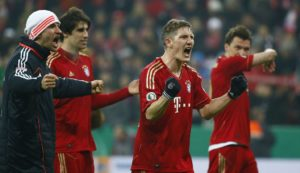 Bayern Munich players celebrate their 1-0 victory over Borussia Dortmund following their German soccer cup, DFB Pokal, quarter final match in Munich