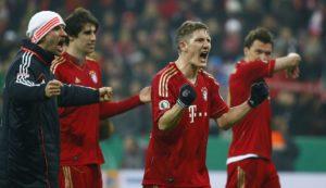 Bayern Munich players celebrate their 1-0 victory over Borussia Dortmund following their German soccer cup, DFB Pokal, quarter final match in Munich